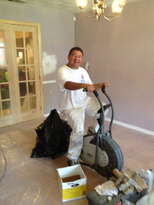 My housepainter, Esperanto Espiritu, takes a break from the job of painting my house and catches a few laps on the 1980's era stationary bike left by the previous owner, inexplicably still siting in the middle of my formal dining room.