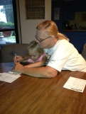 Granny Wilma assists my baby girl in filling out her score sheet.